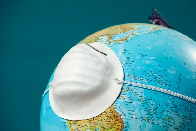 Лекарственная маска для лица на глобус. мировая эпидемия коронавирусной концепции.