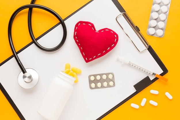 Medicine falling from bottle over clipboard; stethoscope; stitched heart shape; injection; blister packed medicine against yellow desk