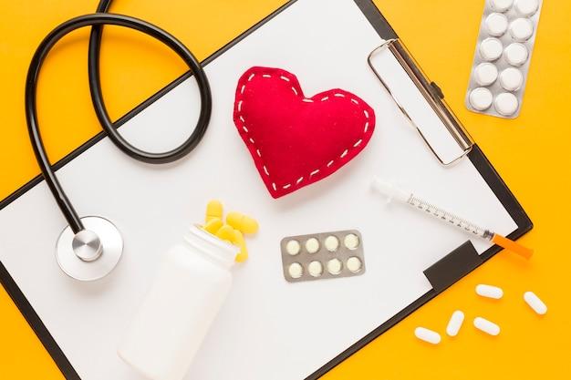 Медицина падает из бутылки над буфером обмена; стетоскоп; сшитая форма сердца; инъекции; лекарство в блистерной упаковке против желтого стола