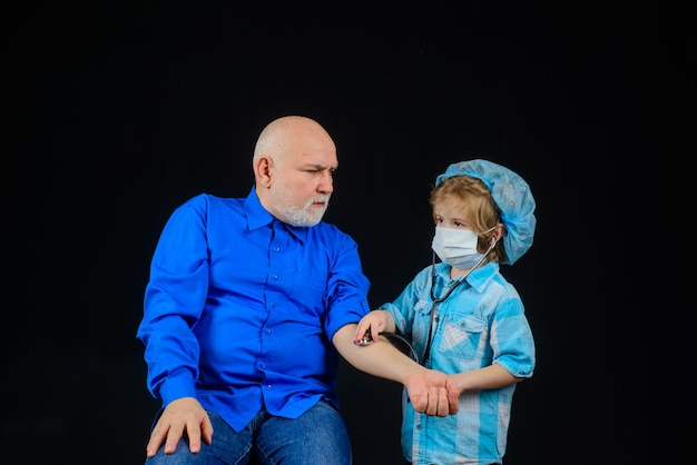 Medicine game boy doctor playing with grandfather treatment home treatment doctor game kid play
