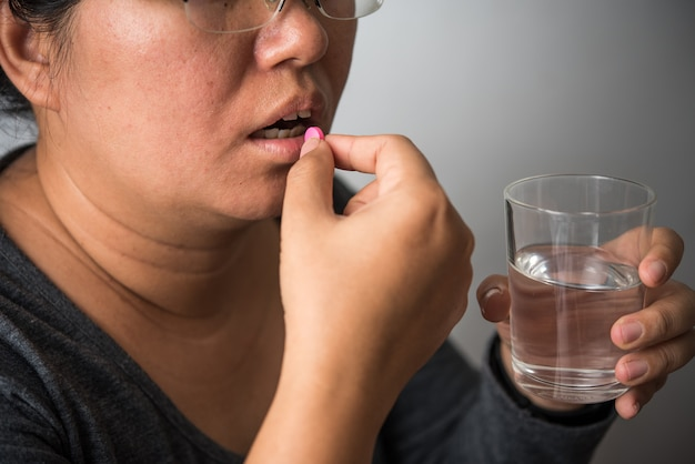 Medicine and a glass of water in the hands of the female for sick