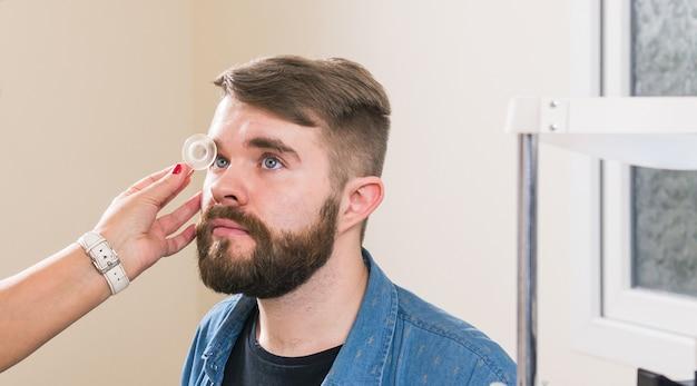 Концепция медицины, здоровья, офтальмологии - офтальмолог исследует глаза пациента.