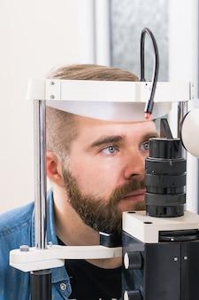 Концепция медицины, здоровья, офтальмологии - пациент проверяет свое зрение у офтальмолога.
