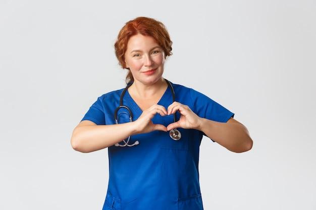 医学、ヘルスケア、コロナウイルスの概念。思いやりのある中年の女性看護師、心臓のジェスチャーを示し、笑顔を見せて、退職後の家で患者の世話をしているスクラブの医者、灰色の背景。