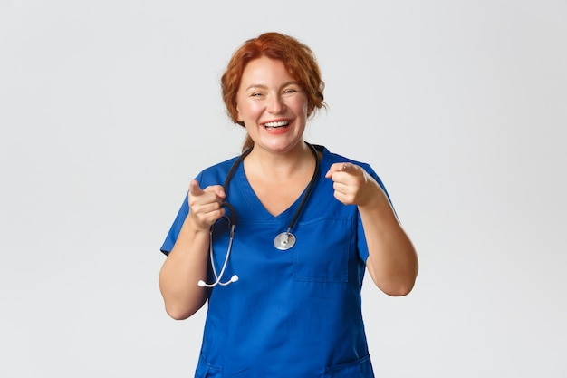 Концепция медицины, здравоохранения и коронавируса. веселый, восторженный рыжий медицинский работник, женщина-врач в скрабах, указывая пальцами на камеру и улыбаясь, приглашая вас, восхваляя хороший выбор.