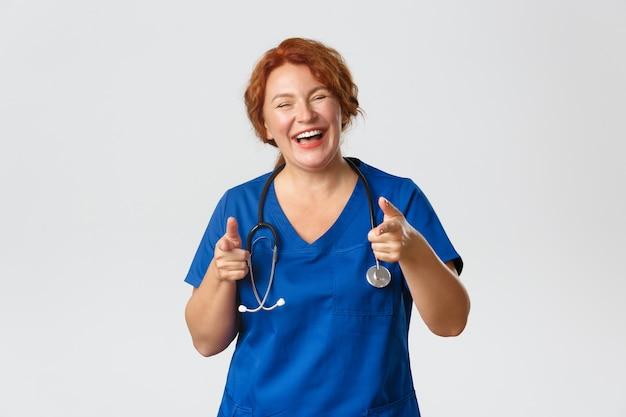 医学、ヘルスケア、コロナウイルスの概念。陽気で熱狂的な赤毛の医療従事者、スクラブの女性医師が指のカメラを指して、のんびりと笑い、あなたを招待し、良い選択を賞賛します。