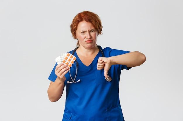 医学、ヘルスケア、コロナウイルスの概念。ひどい薬を見せて、悪い薬を持っている失望した顔をゆがめた中年の女性医師は、このビタミンや錠剤をお勧めしません。親指を下に向けて表示します。