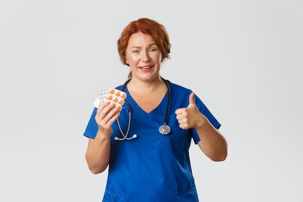 医学、ヘルスケア、コロナウイルスの概念。笑顔の赤毛の女性医師、インフルエンザ、インフルエンザ、またはアレルギーからのアドバイス治療として親指を立てる医師、錠剤を示す医師は、ピルをお勧めします。