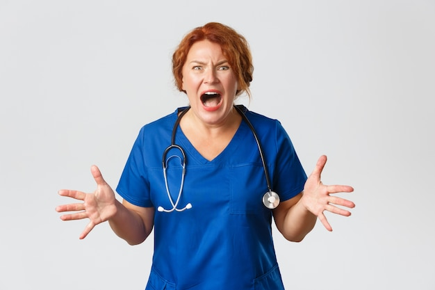 Medicine, healthcare   concept. anxious and frustrated, screaming female doctor, nurse going nuts, shouting, shaking hands, losing temper and feeling mad, standing over  .