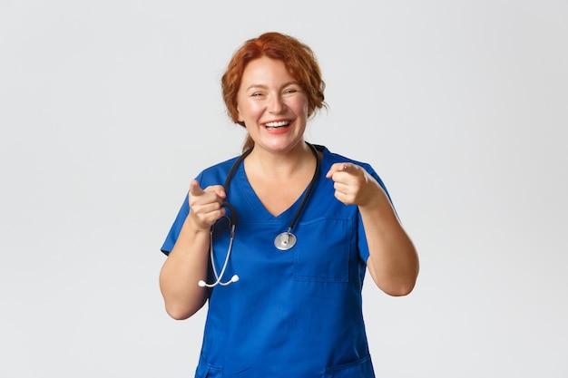 医学、ヘルスケアの概念。陽気で熱狂的な赤毛の医療従事者、スクラブをしている女性医師がカメラに指を向けて微笑んで、あなたを招待し、良い選択を賞賛します。