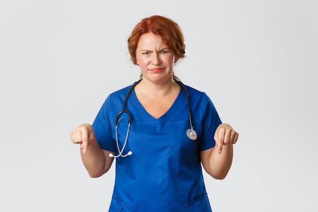 医学、ヘルスケアの概念。懐疑的で失望した赤毛の女性医師、看護師、または医療従事者が、指を下に向けて、顔をゆがめた顔をしかめる。