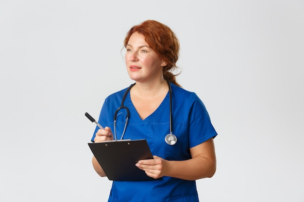Medicine, healthcare and coronavirus concept. focused female doctor taking notes, checkup on patient, listening to person complaints in clinic, writing down clipboard, standing in scrubs.