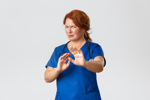 Medicine, healthcare and coronavirus concept. reluctant and displeased redhead female doctor, nurse asking to stay away, extend hands in rejection and grimacing, cringe from aversion, grey background.