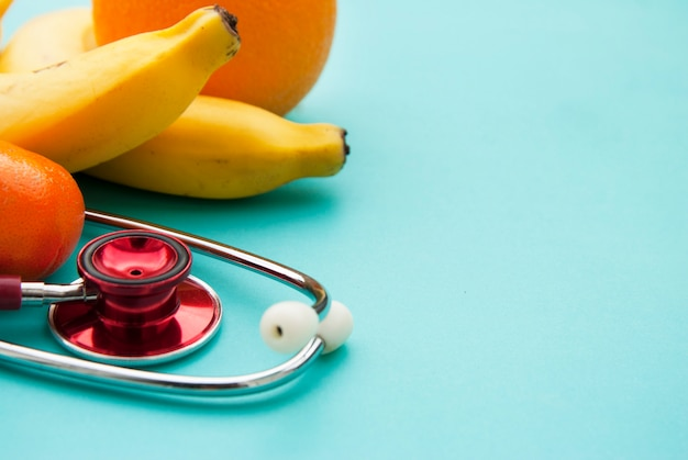 Medicine and healthcare, nutritionmedical insurance over blue . fruits and red sthetoscop. copyspace.