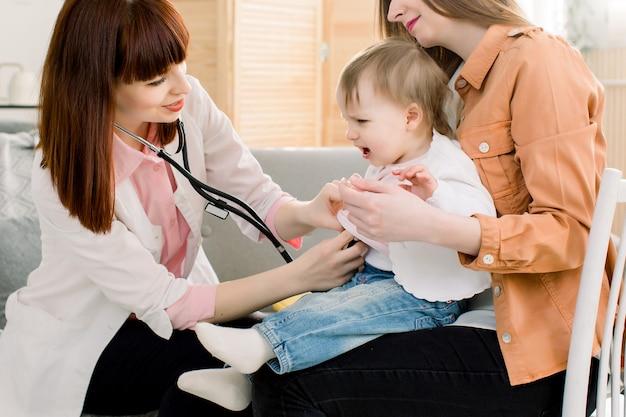 Медицина, здравоохранение, педиатрия и люди концепции - мать с ребенком на руках у педиатра, чтобы исследовать, маленькая девочка плачет