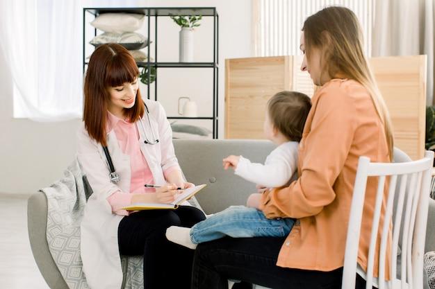 Медицина, здравоохранение, педиатрия и люди концепции - портрет молодой женщины педиатра, делая рецепт для молодой матери и ее ребенка
