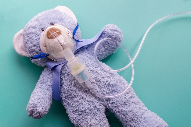 Medicine layout or flat lay. children's toy masked by inhaler. the blue bear symbolizes the child and childhood.