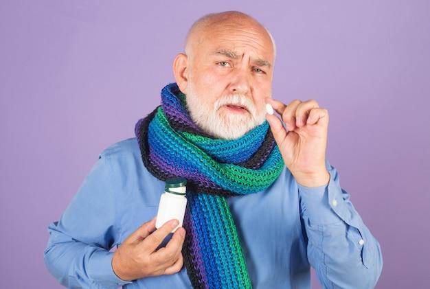 薬。錠剤を持つ男。冬の寒さ。インフルエンザ。治療薬。