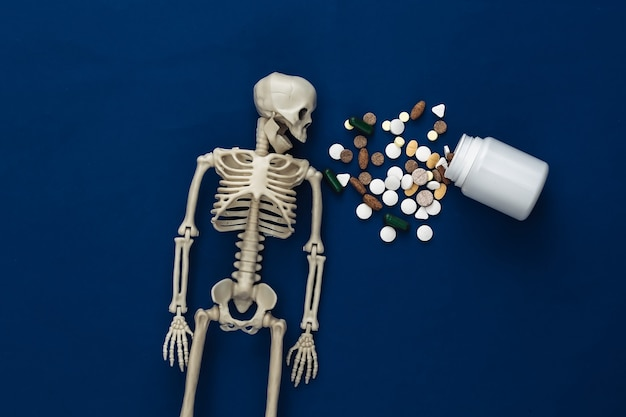 Medicine or narcotic concept concept. skeleton and bottle of pills on classic blue