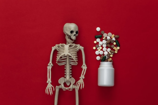 Medicine or narcotic concept concept. skeleton and bottle of pills on red