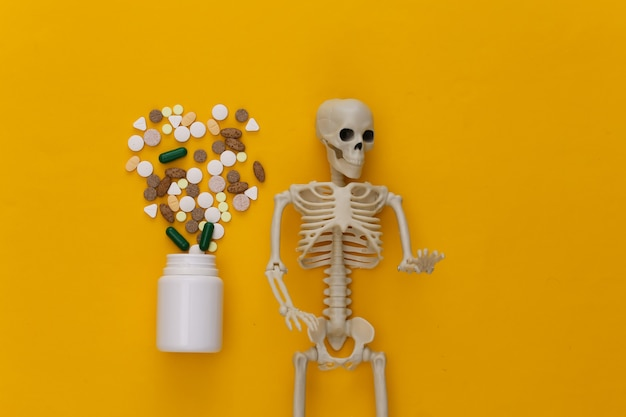 Medicine or narcotic concept concept. skeleton and bottle of pills on yellow