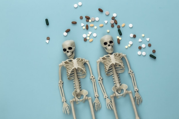 Medicine or narcotic concept concept. skeletons and pills on blue