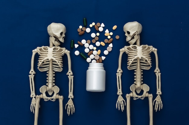 Medicine or narcotic concept concept. two skeletons and bottle of pills on classic blue