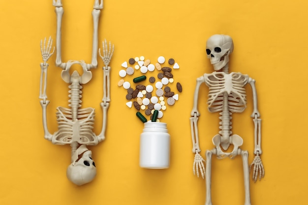 Medicine or narcotic concept concept. two skeletons and bottle of pills on yellow