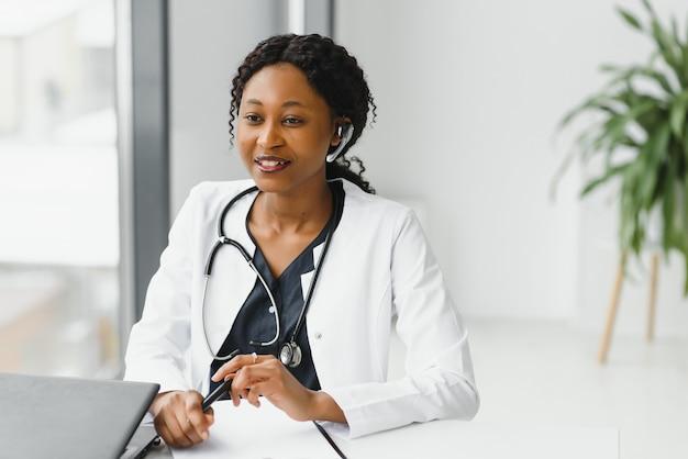Медицина, онлайн-счастливая улыбающаяся афро-американская женщина-врач или медсестра с гарнитурой и ноутбуком, проводящая конференцию или видеозвонок в больнице