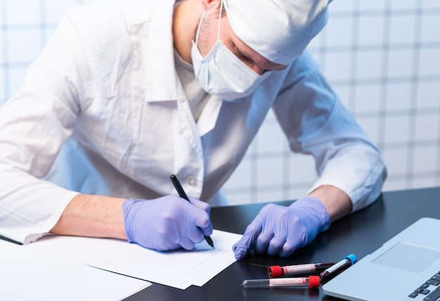 Medicine, people and healthcare concept  close up of male doctor writing medical report to clipboard at hospital
