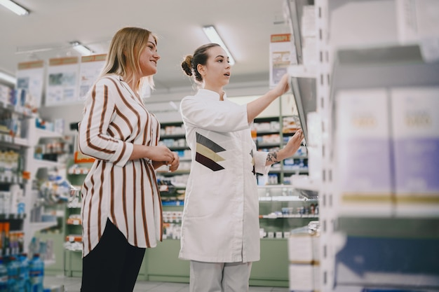 医学、薬剤学、ヘルスケアおよび人々の概念。女性薬剤師が購入者にアドバイスします。