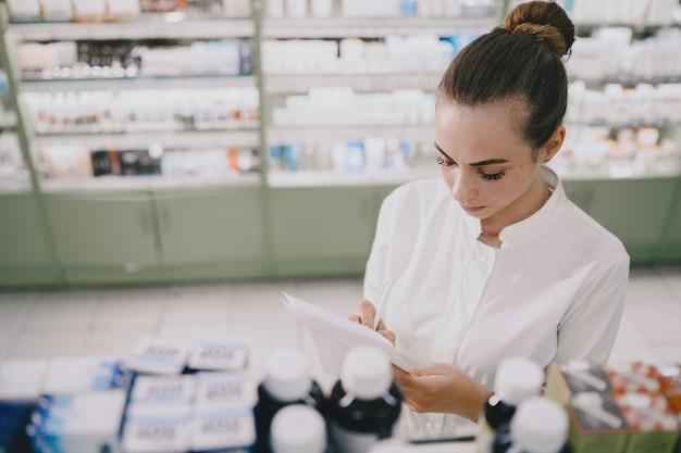 Концепция медицины, фармацевтики, здравоохранения и людей. женский фармацевт принимает лекарства с полки.