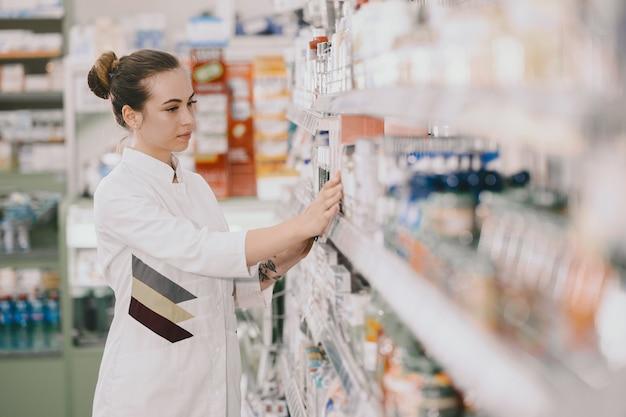 의학, 조제 학, 건강 관리 및 사람들 개념. 선반에서 약물을 복용하는 여성 약사.