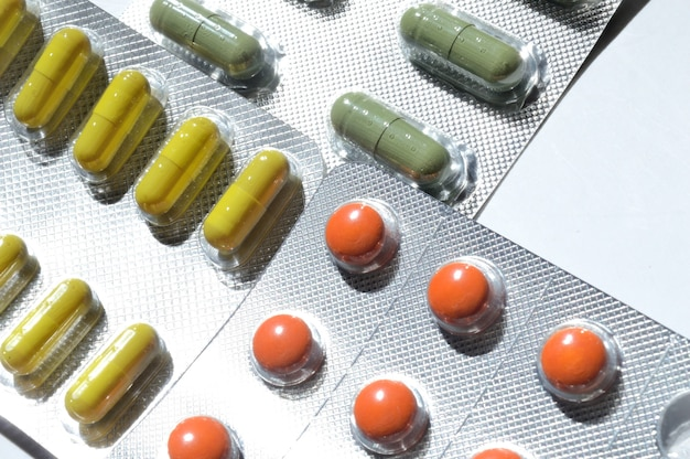 薬の丸薬は水ぶくれに詰め込まれ、明るい背景に横たわっています。閉じる。