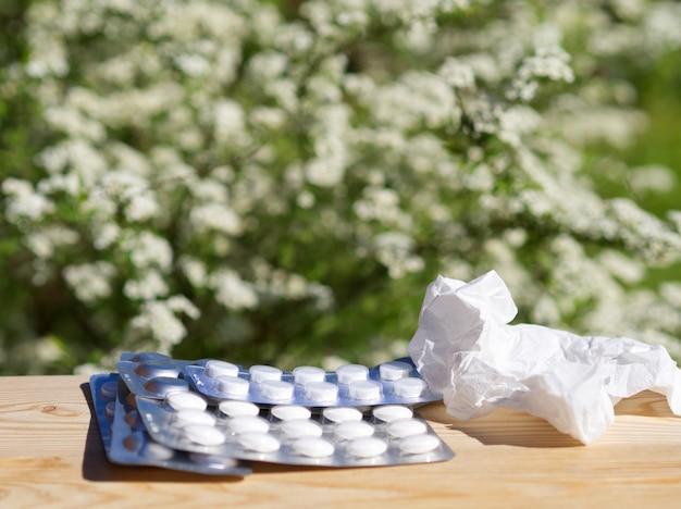 Medicine pills, handkerchief on table on green nature background