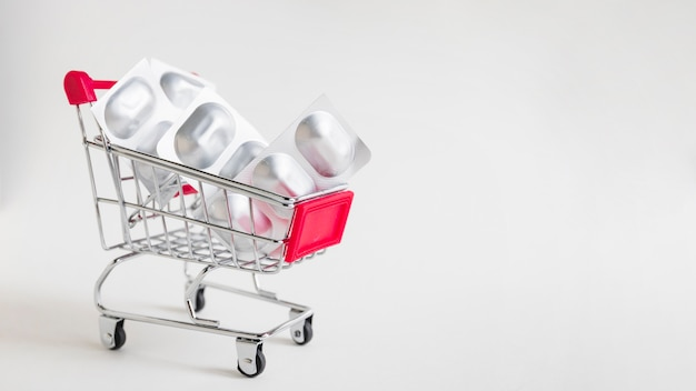 Medicine pills pack in miniature shopping cart on white background
