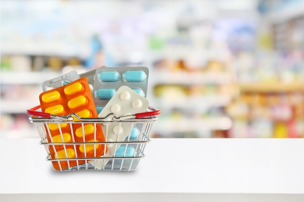 薬局のドラッグストアの棚が背景をぼかすショッピングバスケットの薬の丸薬パッケージ