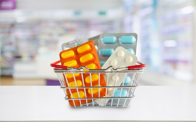 Medicine pills in shopping basket with pharmacy drugstore