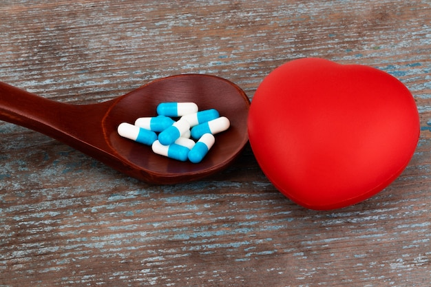 Medicine pills, tablets and capsules on wooden spoon with heart.