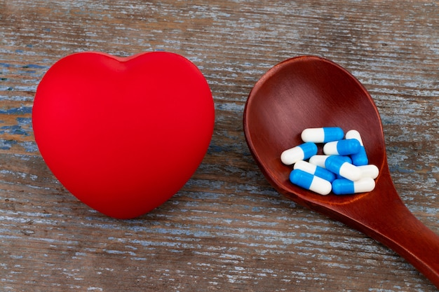 Medicine pills, tablets and capsules on wooden spoon with heart