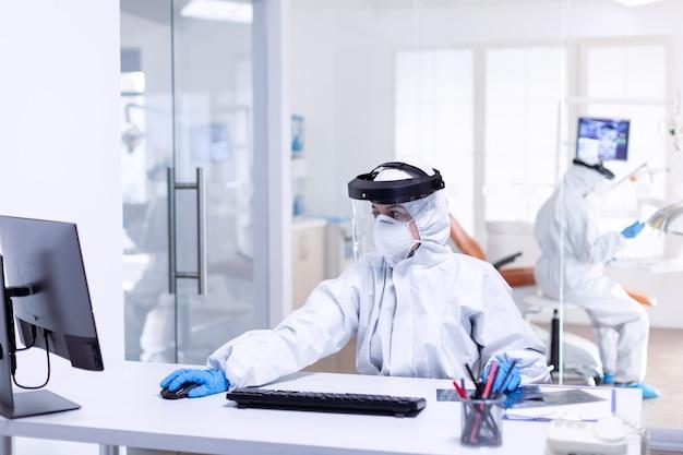 コンピューターを使用した安全対策として、covid19でおしっこスーツを着た開業医。安全予防策として歯科レセプションでコロナウイルスパンデミックに対する保護装置を身に着けている医学チーム