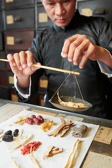 朝鮮人参の根を重み付けする開業医