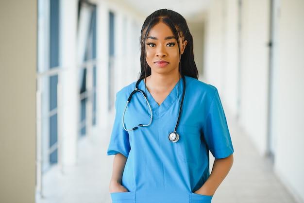 Концепция медицины, профессии и здравоохранения - счастливая улыбающаяся афро-американская женщина-врач со стетоскопом на фоне больницы