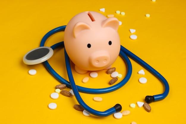 医学の静物。聴診器付きの貯金箱、黄色の錠剤。