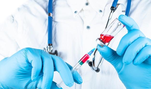 医師または看護師の手に針とアンプルを備えた薬の予防接種装置。