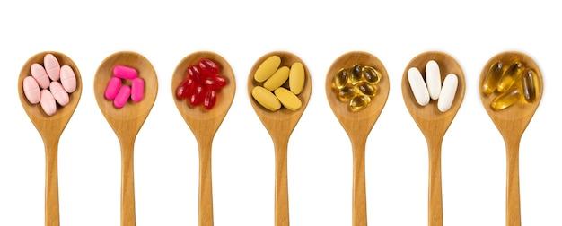 白で隔離の木のスプーンで薬、ビタミン、サプリメント