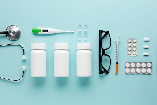 Medicines and healthcare accessories arranged on blue surface