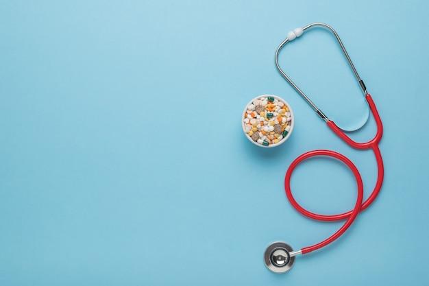 세라믹 그릇에 약과 파란색 배경에 빨간색 청진 기. 텍스트를 위한 공간입니다. 플랫 레이.