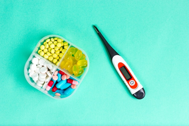 알약 상자에 있는 약과 전자 온도계 위에 있는 상자 보기에 있는 여러 가지 빛깔의 비타민