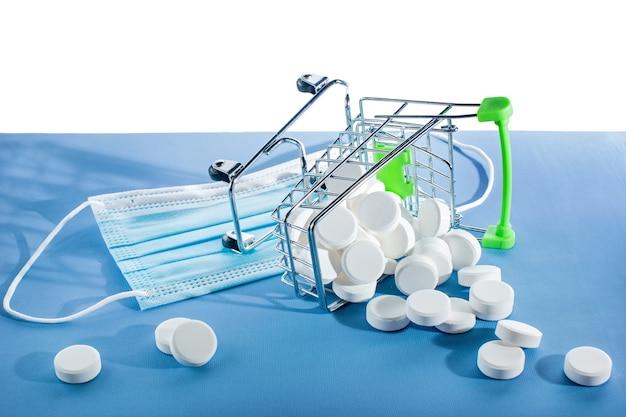 Лекарства в тележке супермаркета и медицинские маски на белом фоне. таблетки и флаконы с наркотиками на белой стене